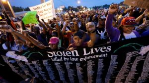People protest the police shooting death of Michael Brown a week ago in Ferguson, Mo., Saturday, Aug. 16, 2014. | Image Courtesy of abcnews.go.com